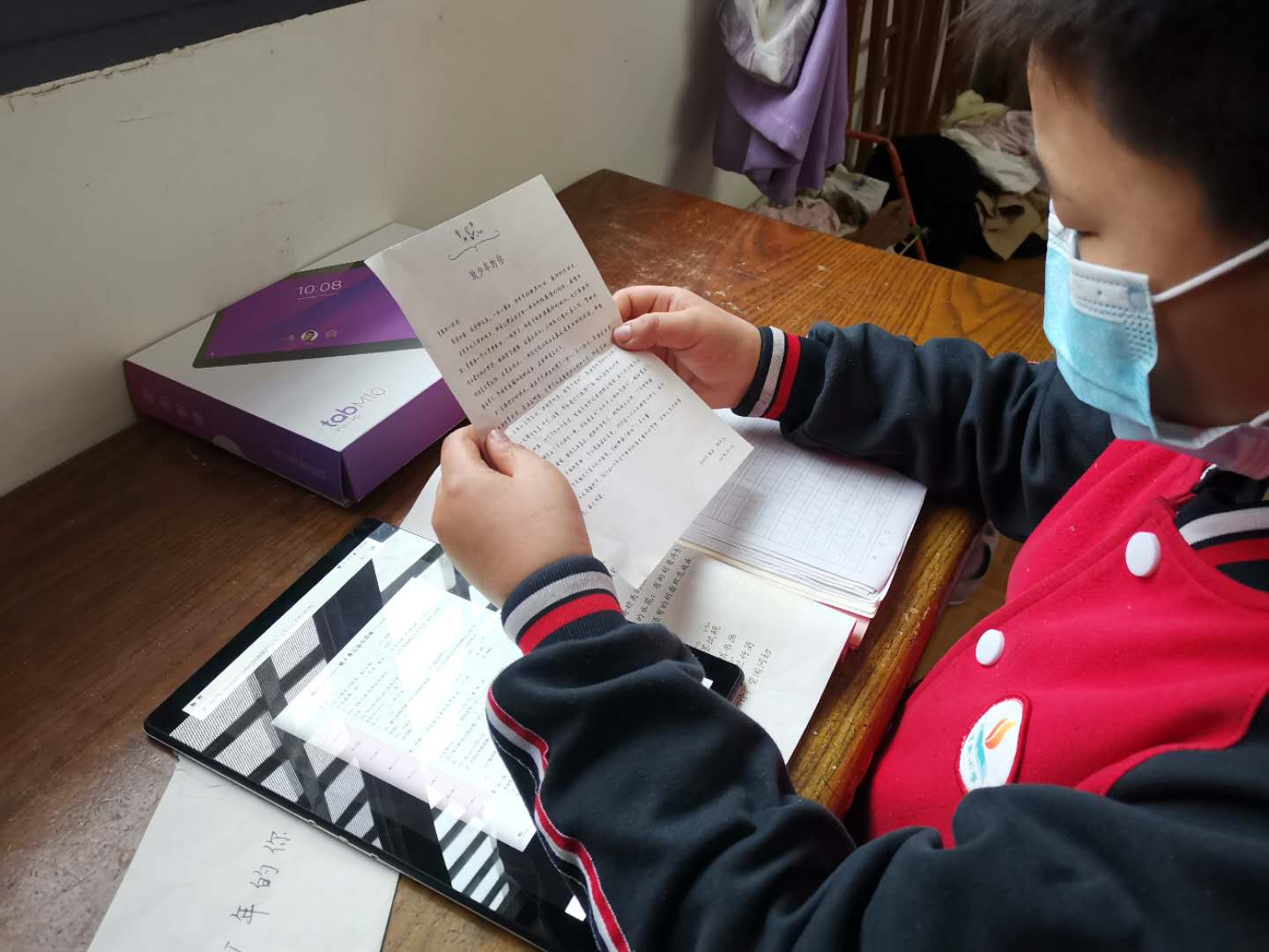 A student in Hubei Province using his new tablet and reading the letter from Lenovo CEO Yuanqing Yang.