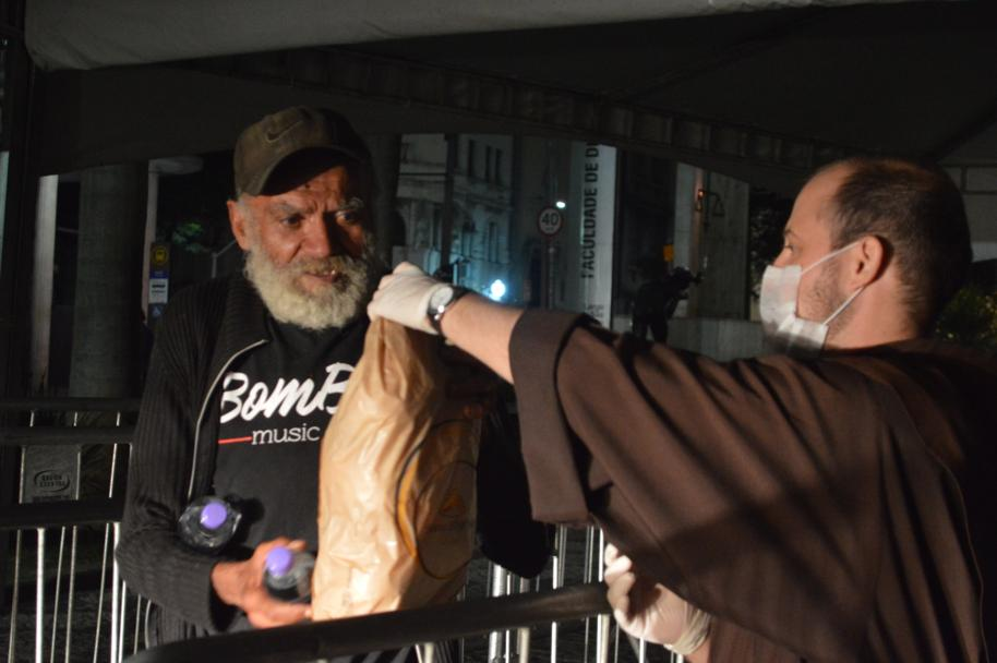 Franciscan monk giving food to the homeless in Sao Paulo