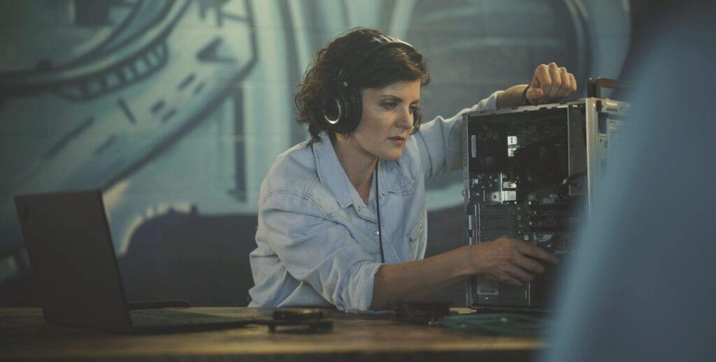Woman working with an open desktop PC and ThinkPad