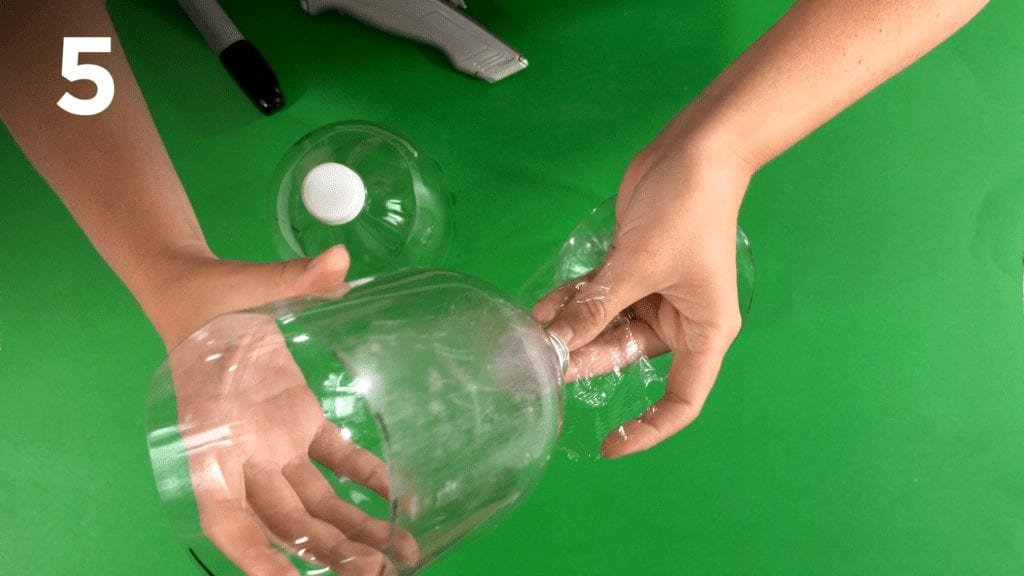 Secure plastic wrap around the bottom of the soda bottle with a rubber band.