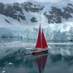 Sailboat with raised red sails moving toward glaciers and snowy mountains.