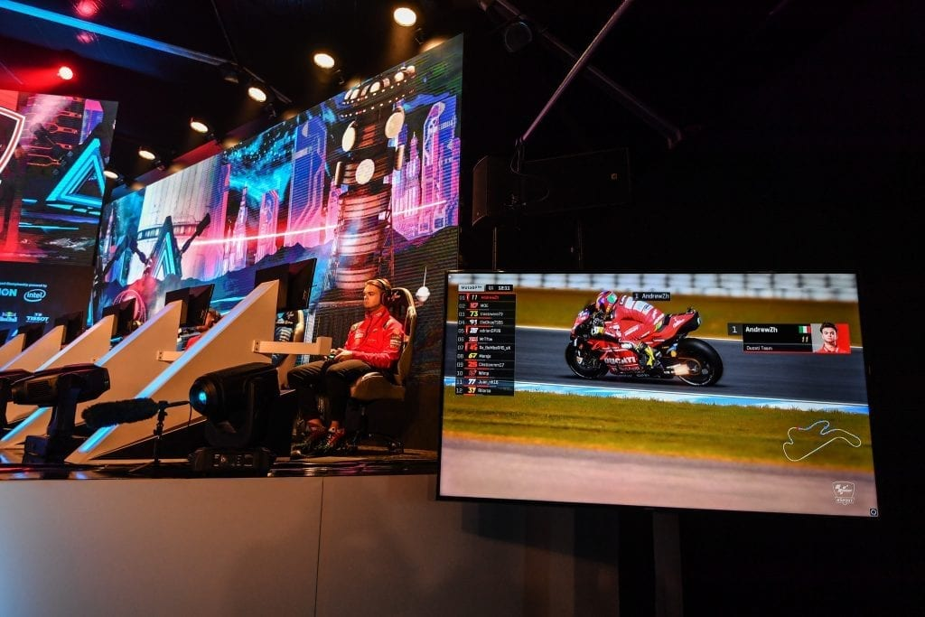 eSport tournament image with the live player at a console while a separate screen shows their view to the audience.