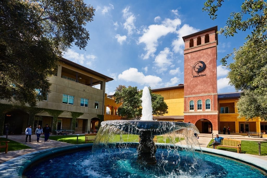 DreamWorks Animation campus with a large fountain in the foreground, people walking in the distance, and the DreamWorks logo visible on a brick building.