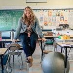 Teacher Jess Smith in an empty classroom, holding herself up between two chairs.