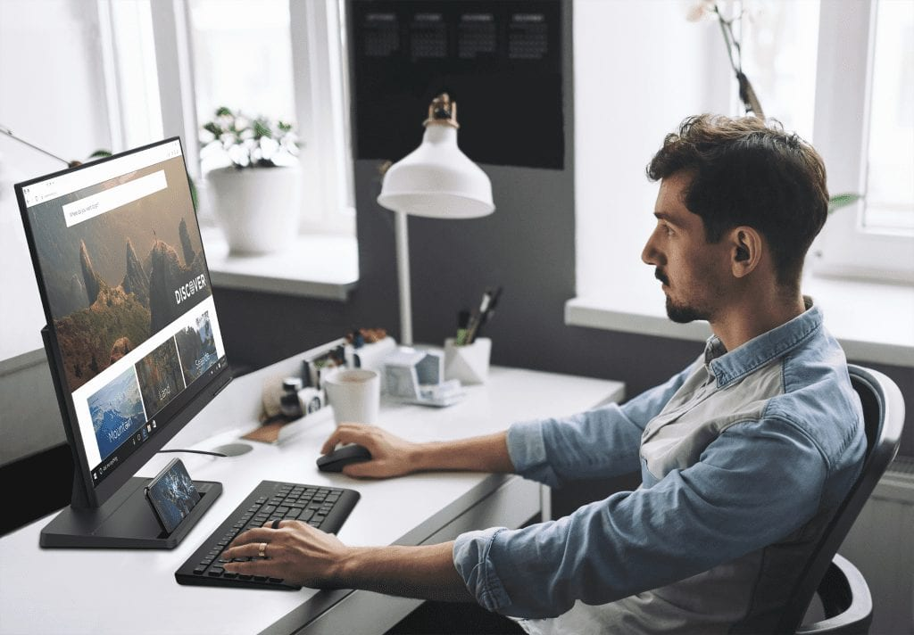 The new Lenovo L27e-30 Monitor seen in use by a person sitting in profile with keyboard and mouse