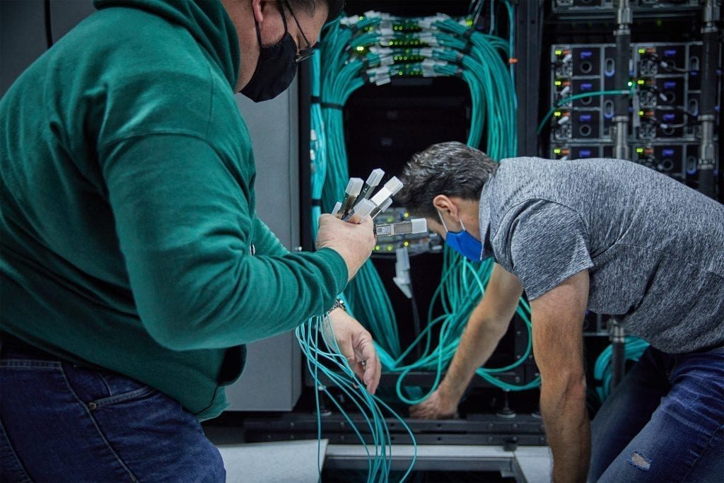Two people holding cables as they install the servers for DreamWorks Animation