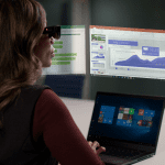 Woman wearing the ThinkReality A3 headset while sitting at a Lenovo laptop with a virtual desktop projected above