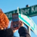 Person holding up their smartphone and aiming it at a MLK, Jr. street sign to activate the AR experience