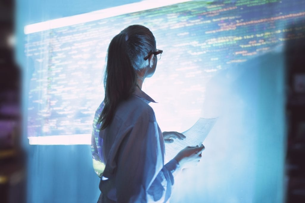 Woman in front of a detailed projection of some kind of data schematic.