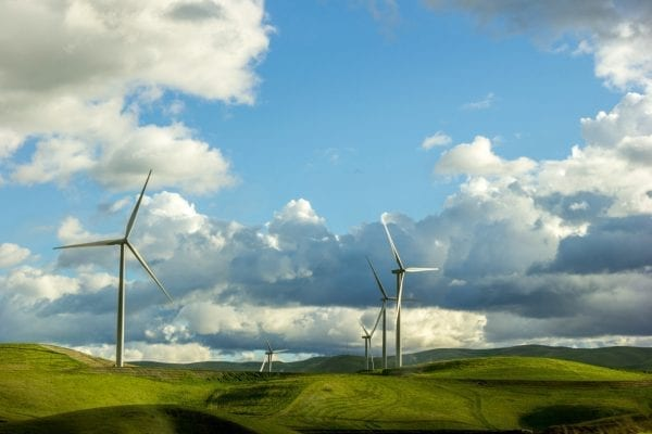 Lenovo brand image - wind turbines on low hills with a blue and partly cloudy sky