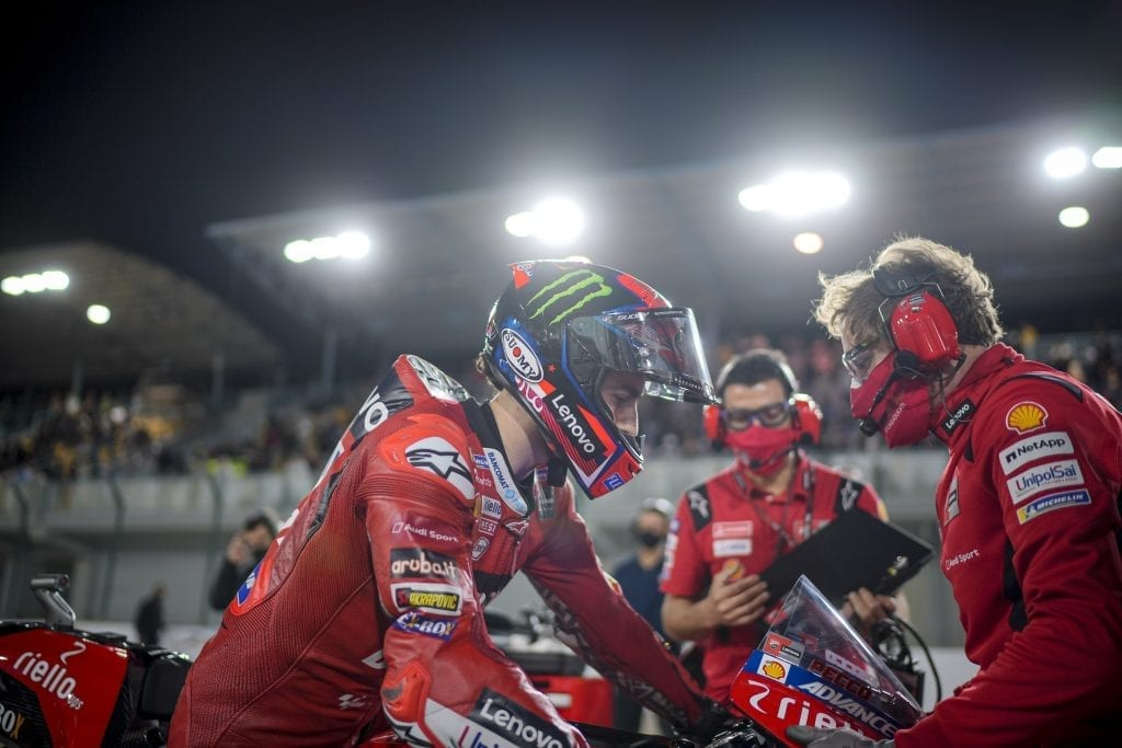 Ducati racer seated on the motorbike in the foreground with team members in the back