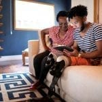Lenovo brand image - older woman and younger man (with prosthetic legs) looking at a handheld device together