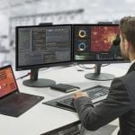 Person sitting with ThinkPad P15 Gen 2 on a desk hooked up to two external monitors.