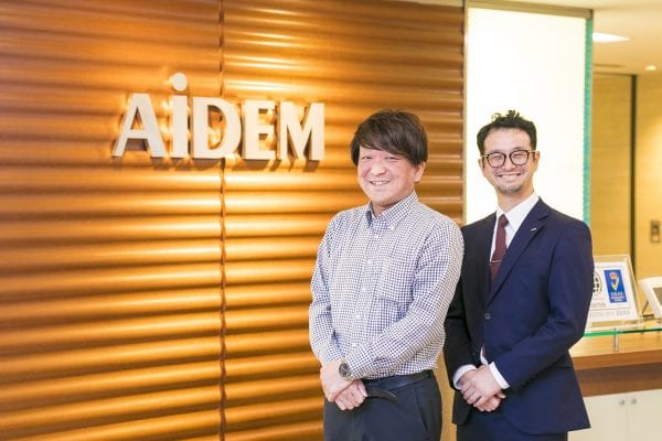 Two executives from AiDEM in front of company sign in an office