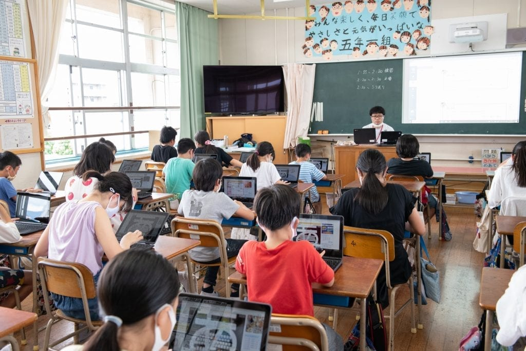 Wide shot of students in a Japanese classroom, wearing masks and using Lenovo PCs