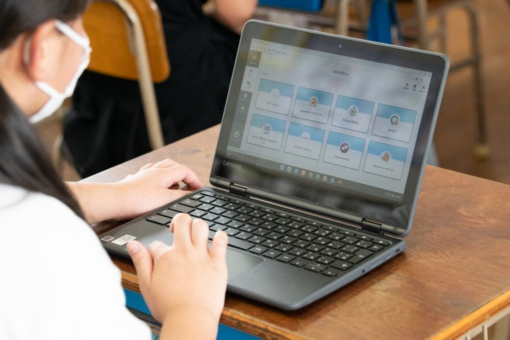 Japanese student using a Lenovo PC to do work in the classroom.
