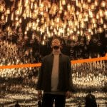 Lenovo Beyond Boundaries image - orange ribbon moving behind a man standing in a mirrored room with a ceiling covered in dozens of light bulbs