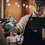 321 Coffee employee passing a bag of coffee to a customer while using a Lenovo ThinkPad