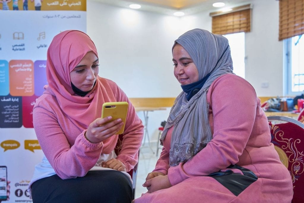 """""""I Learn from Home"""" with Seenaryo / students looking at a phone together"""