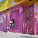 Woman sitting outdoors in front of walls and gates painted bright pink, using a Lenovo device