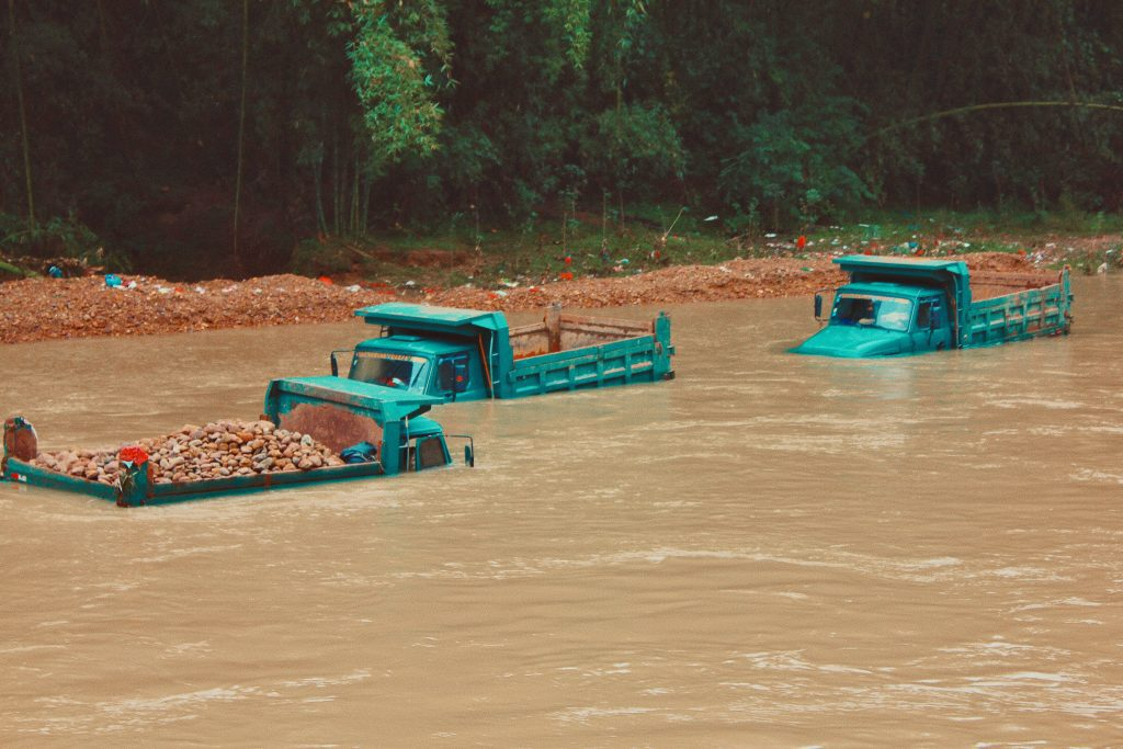 Large trucks almost entirely submerged in flood water