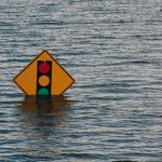 Traffic sign partially submerged in flood waters