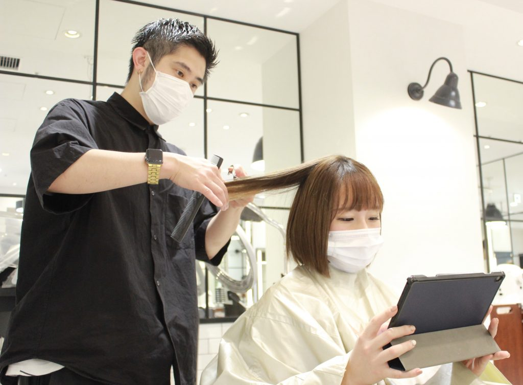 Japan salon with someone using a tablet while getting their hair cut